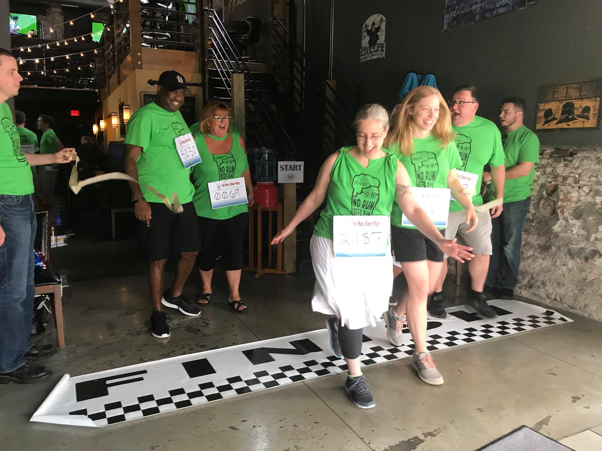 A group of five adults dressed in bright green t-shirts with No Run, Beer Run across the front run through a gold finish line while holding beers.