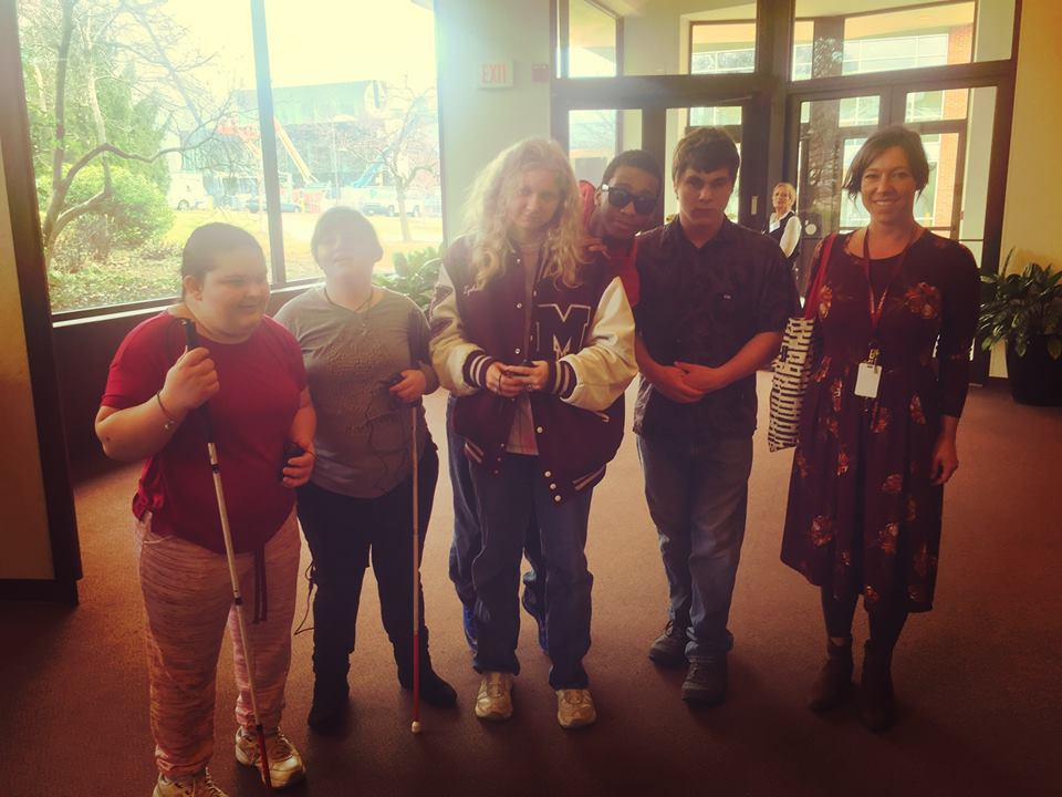 Students from Missouri School for the Blind stand with AD devices in the lobby of The Rep waiting for a performance of To Kill a Mockingbird